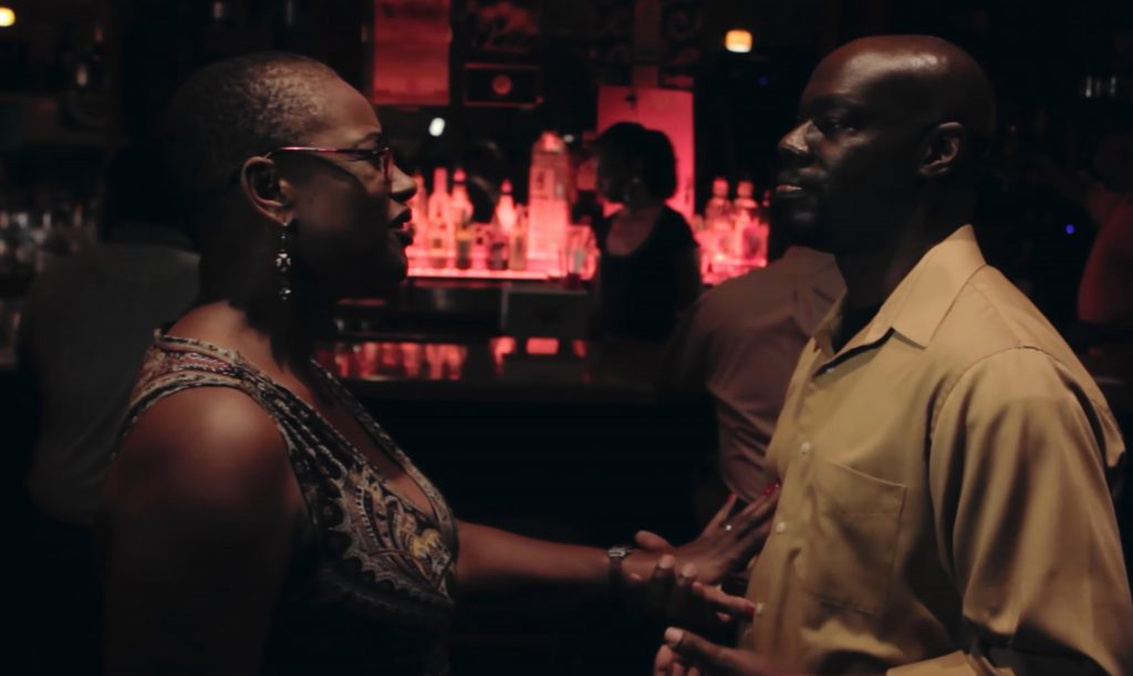a still image from the film Songs For My Right Side featuring a man and a woman at a bar