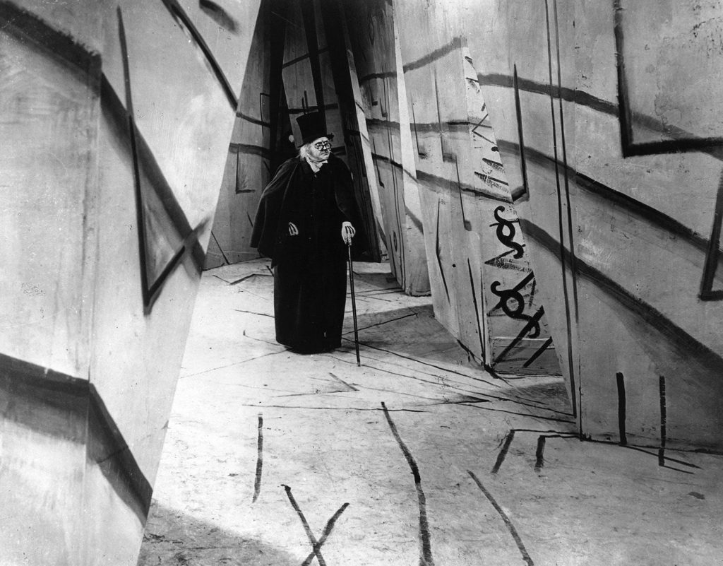 a still from The Cabinet of Dr. Caligari with an old man wearing a black coat and tophat walking in a mysterious hallway