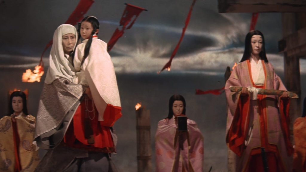 A still from Kwaidan, five people stand wearing robes in front of banners and torches burning