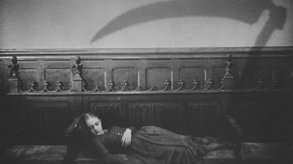 a still from Vampry with a young woman sleeping while a shadow of a scythe is cast on the wall behind her