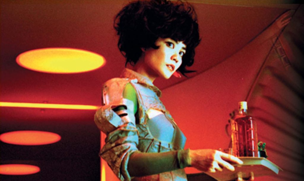 a woman with a beehive hairdo carries a tray with a bottle of liquid on it in a red room