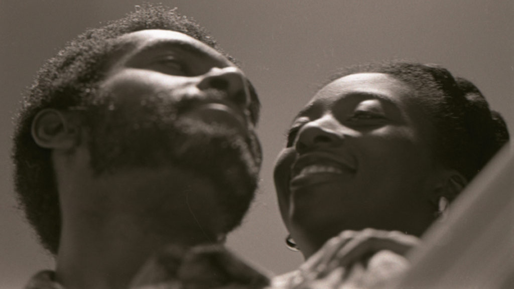 a low angle up on a man and woman smiling at each other