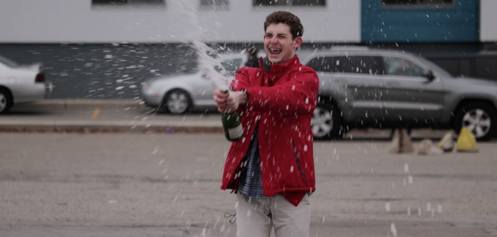 a young man in a red jacket spraying champagne in a parking lot