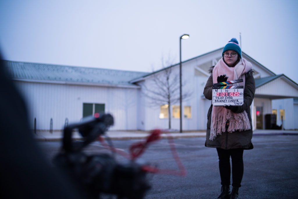 a young woman holds a digital slate in front of a cinema camera on the set of a film