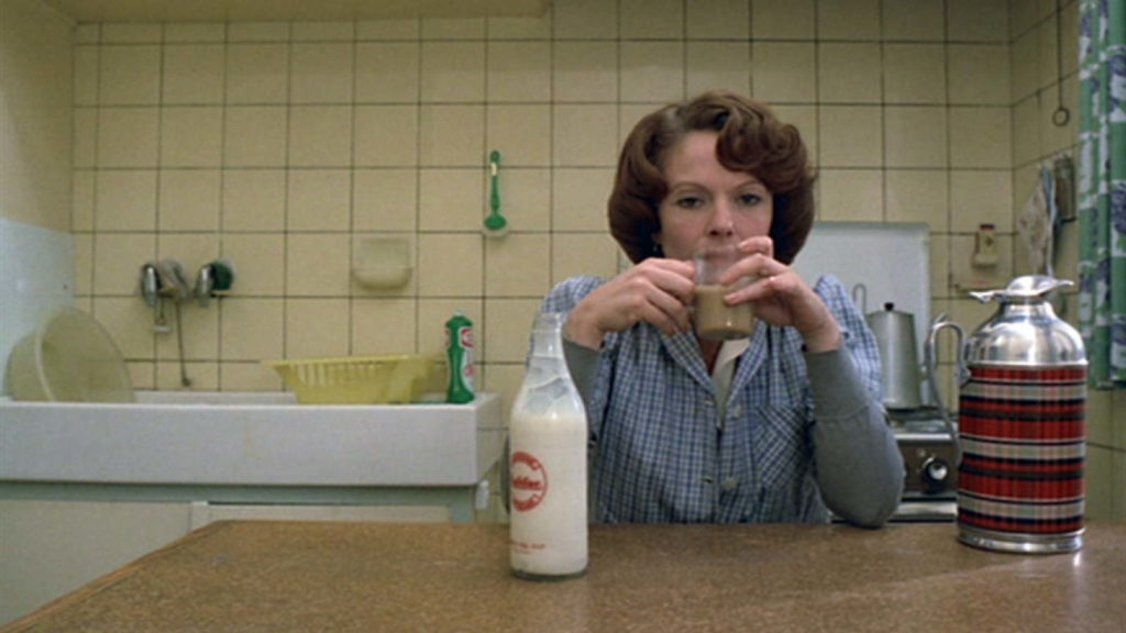 a woman at her kitchen table drinking a mug of tea with a bottle of milk in front of her