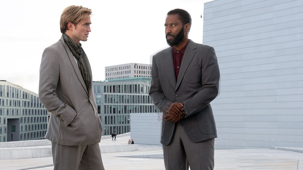 two men in grey suits stand on top of a building