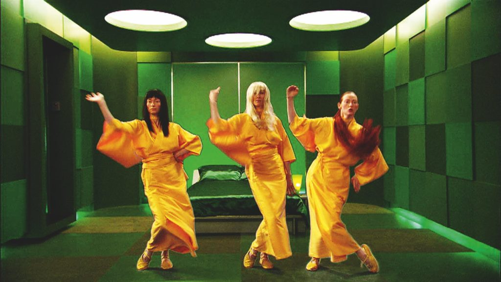 three women in long yellow dresses dancing in a green room