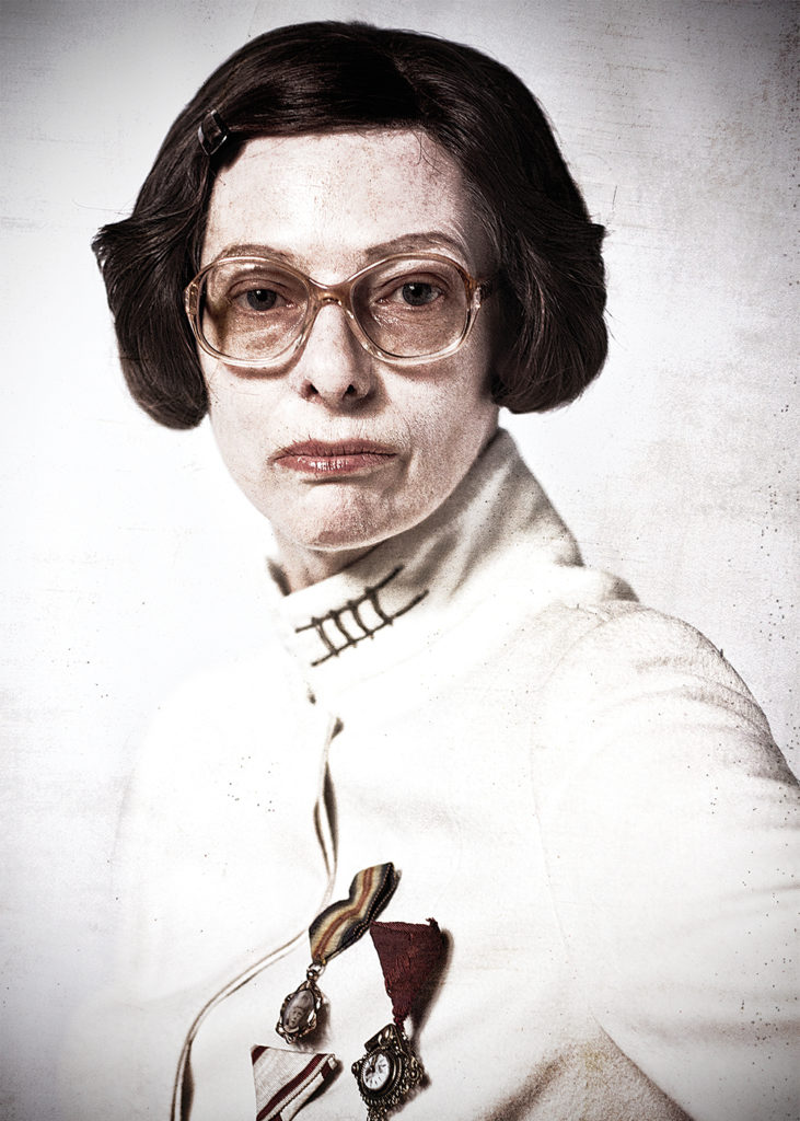 a woman with a brown bob, old fashioned glasses, pursed lips and a military medal on their chest