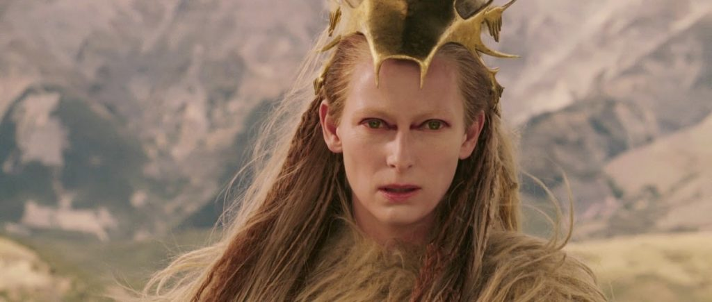 a severe looking woman wearing a gold crown with long hair