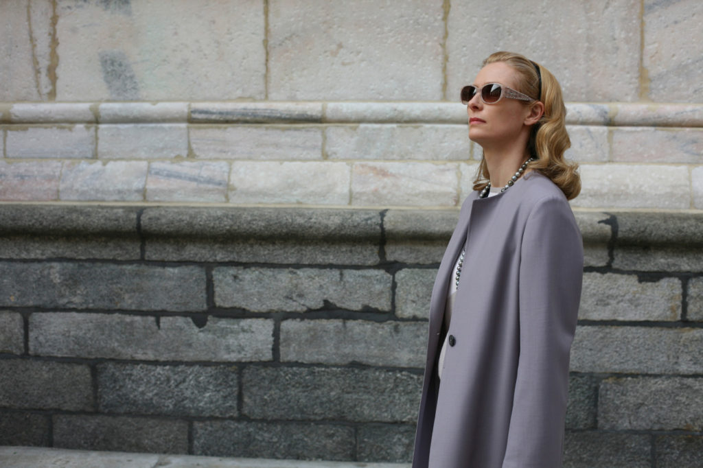 a woman in a grey trench coat and sunglasses