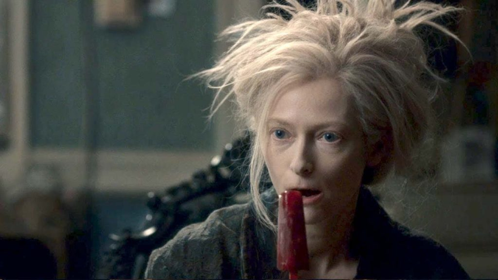 a woman with messy blonde hair eating a dark red popsicle