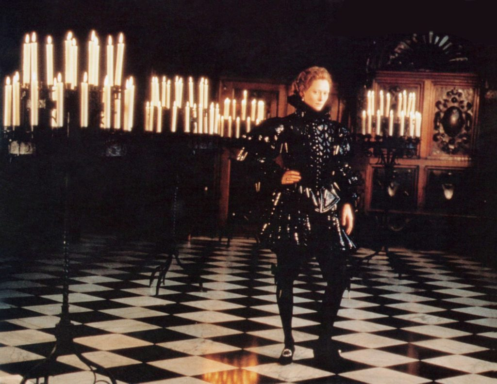 a person in Elizabethan garb in a room lit by dozens of candles