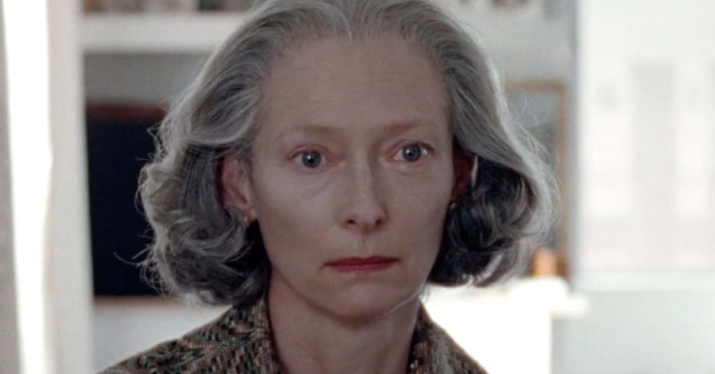 a woman with grey hair and sad eyes