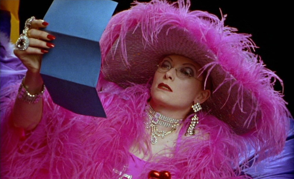 a woman with a hot pink feathered dress and hat holds a blue folded piece of paper