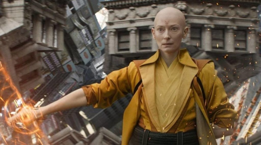 a futuristic looking bald person in yellow with sparks emerging from their hands